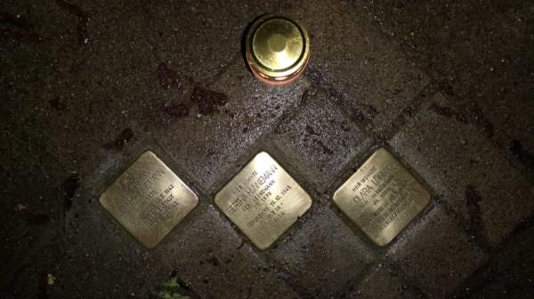 Drei Stolpersteine, die von einer Kerze beleuchtet werden.